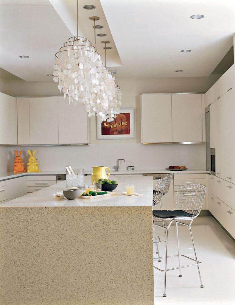Просторная кухня выполненная в светлых тонах с большим кухонным островом в центре комнаты сама по себе может являться местом встречи гостей.