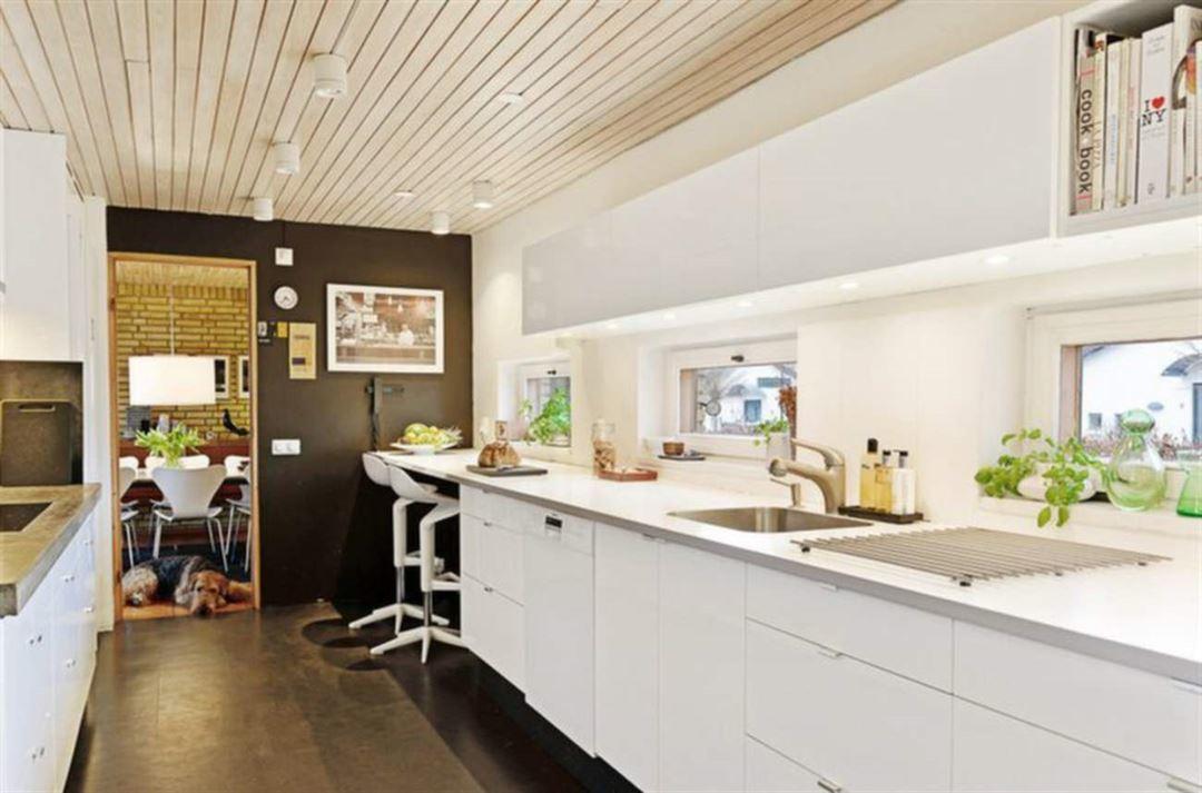 Иной ракурс на кухню. Хорошо видна столовая рядом с кухней. Окна вдоль кухонной столешницы хорошо ее освещают.