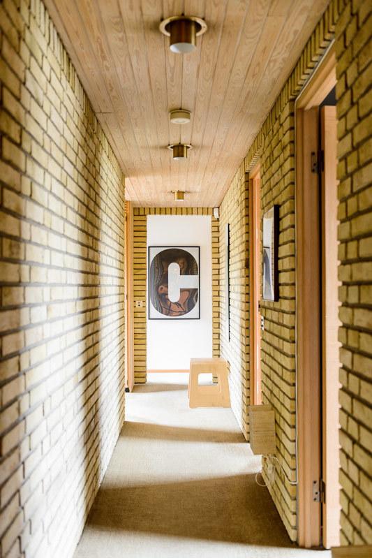 Кирпичные стены сами по себе являются украшением коридора, картины лишь дополняют декор.