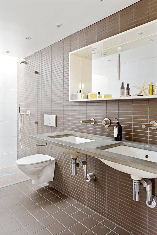 Рядом с главной спальней находится ванна с элегантной коричневой кафельной плиткой, квадратной на полу и прямоугольной на стенах. Подвесной унитаз и легкий сдвоенный умывальник со столешницей из песчаника добавляют помещению объема и легкости.