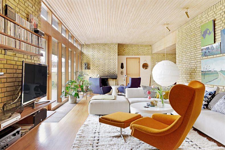 Светлая гостиная с кирпичными стенами, тиковым полом и потолком отделанным сосновой вагонкой.