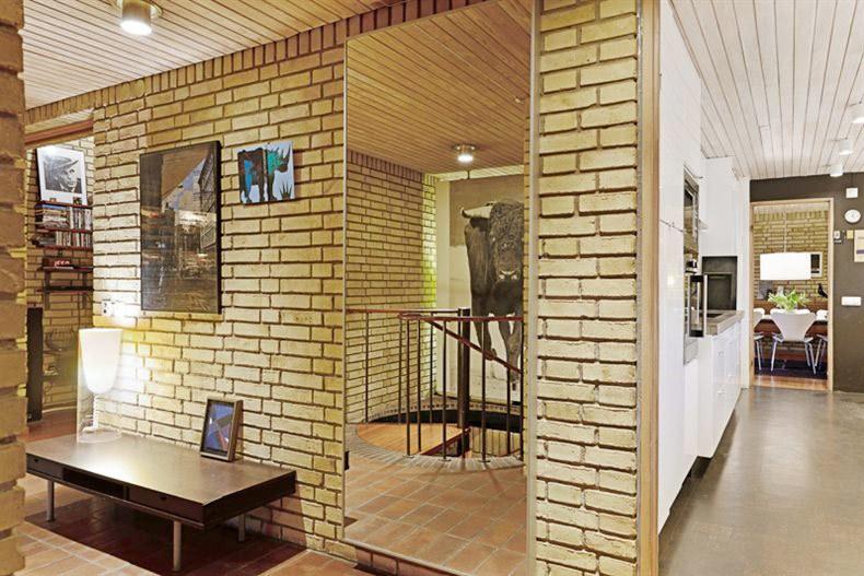 Винтовая лестница отражающаяся в зеркале ведет на этаж со спальней, домашним офисом, гостиной, ванной и сауной.