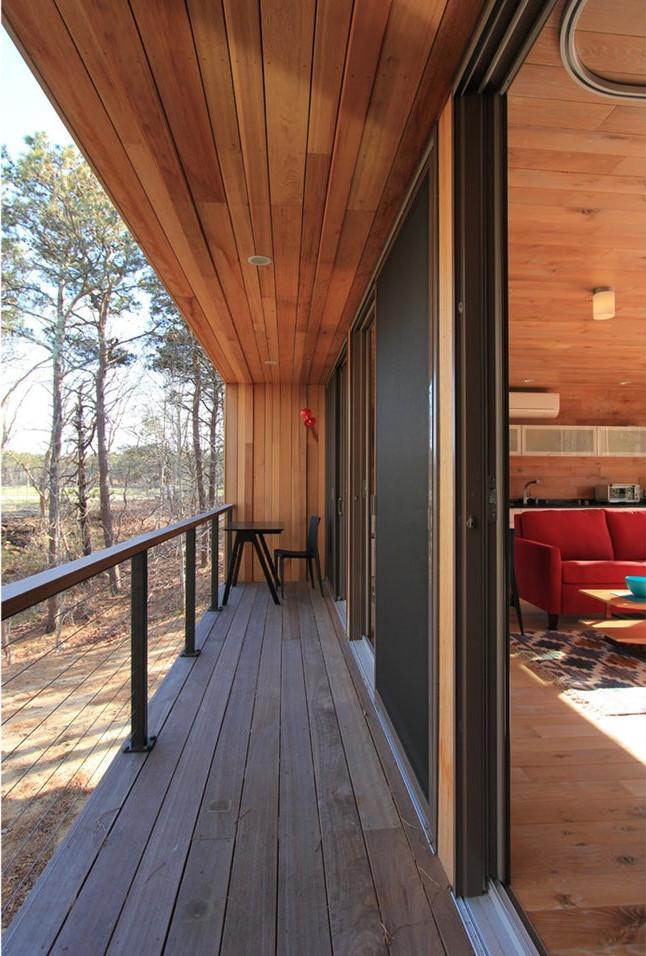 Балкон вдоль противоположной от входа и ванной стены служит единению дома с природой. Сдвижные остекленные двери позволяют выходить на балкон как из жилой комнаты так и из спальни
