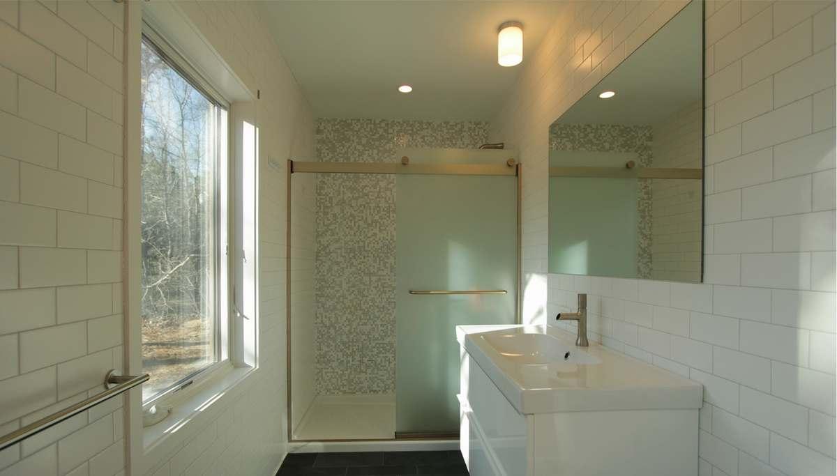 Большая светлая ванна с большим окном совсем не напоминает о маленьком доме.