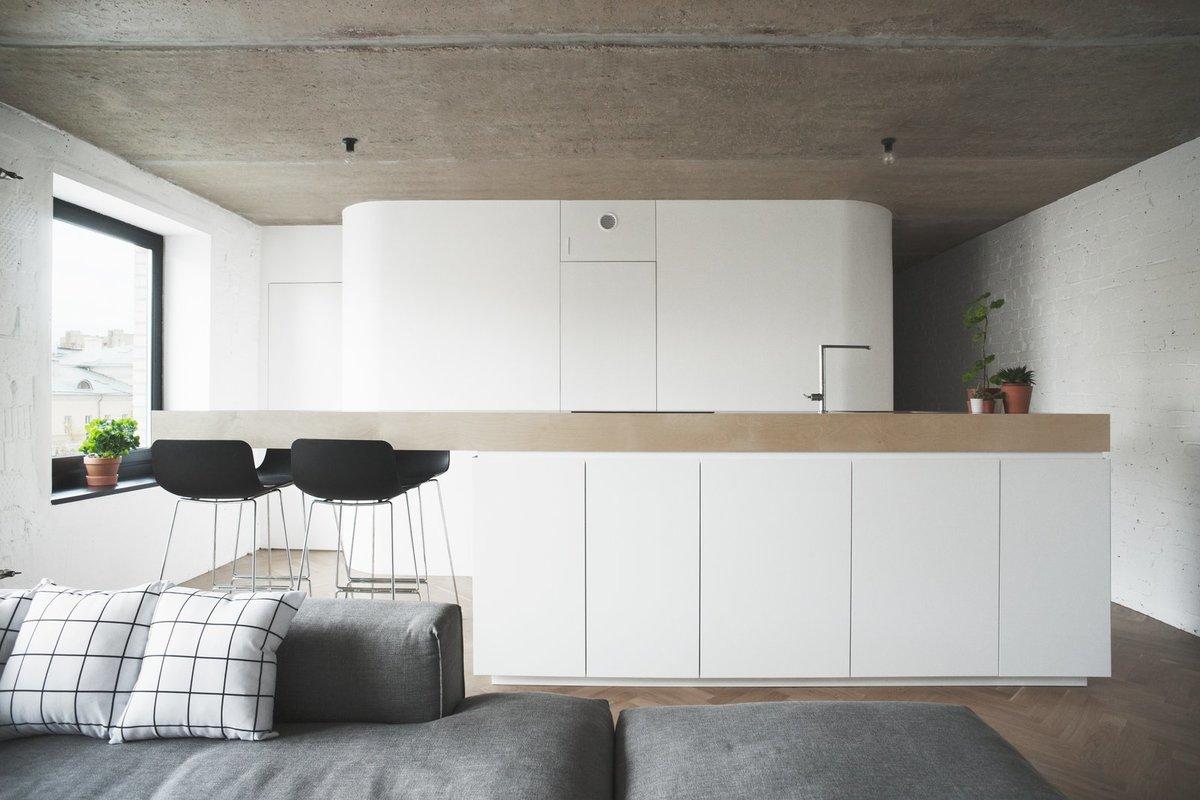 Барная стойка, которая является продолжением столешницы кухонного острова, выступает в качестве обеденного стола в этой небольшой квартире.