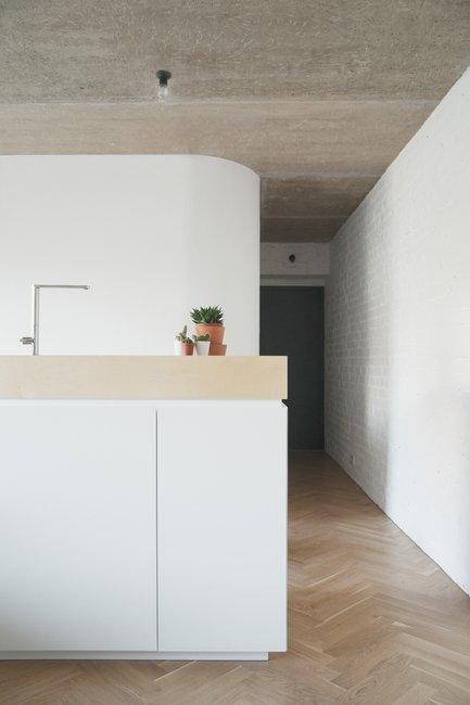 Длинная белая кирпичная стена подчеркивает длину квартиры визуально создавая ощущение большого пространства.