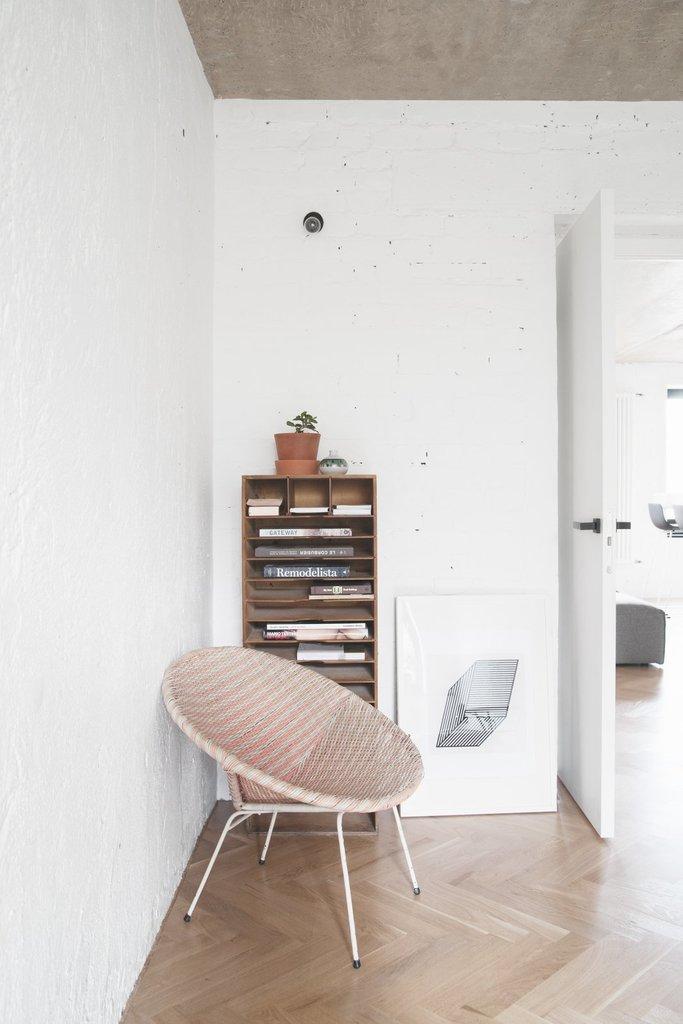 Обычно за дверью в таких узких спальнях располагают плательный шкаф, в данном случае дизайнеры отдали предпочтение винтажному креслу из 60-х и картотеке в качестве книжного шкафа.