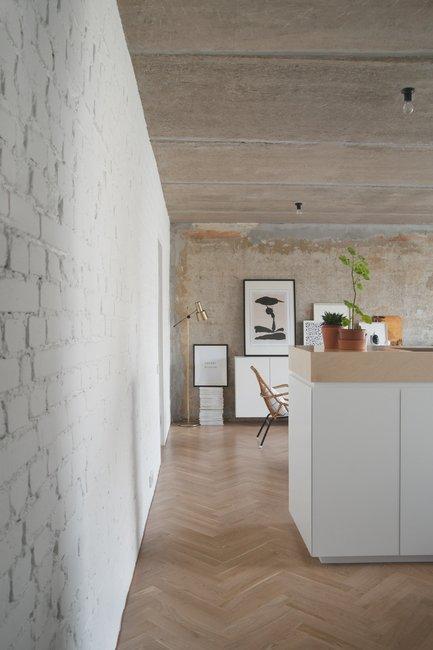 Окрашенная белая кирпичная стена имеет интересную текстуру, однако выглядит не столь брутально как голый бетон, и является своеобразным переходом от белой кухонной мебели к не окрашенной стене и голому бетонному потолку.