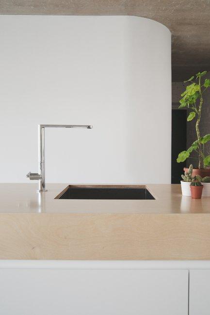 Резкий минимализм в оформлении кухни слегка смягчен зелеными растениями на кухонной столешнице.