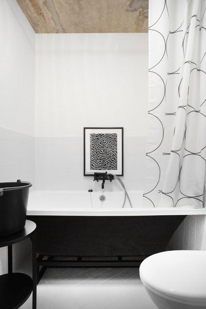 Ванная комната действительно чем-то отдаленно напоминает ванну в квартире советской интеллигенции - простой кафель, высокие, но не крашенные потолки, сдержанная занавеска.