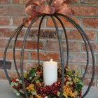 Простой черный светильник из арматуры в виде тыквы украшенный бантом и дарами осени.