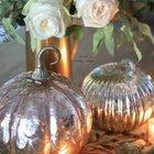 В композиции со свечами свет играет переливами на блестящей поверхности стеклянных тыкв.