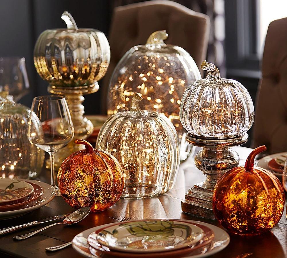 Элегантные тыквы из стекла со светодиодными гирляндами внутри украшают праздничный стол.