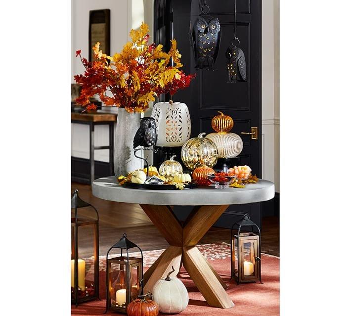 Стеклянные и фарфоровые тыквы в осенней композиции на круглом бетонном журнальном столике.
