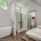 Большая и светлая ванна с душем на втором этаже дома.