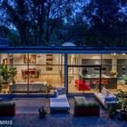 Дом в вечернее время, вид с дорожки в саду за домом. На плоской кровле видны световые фонари, улучшающие освещенность. ()