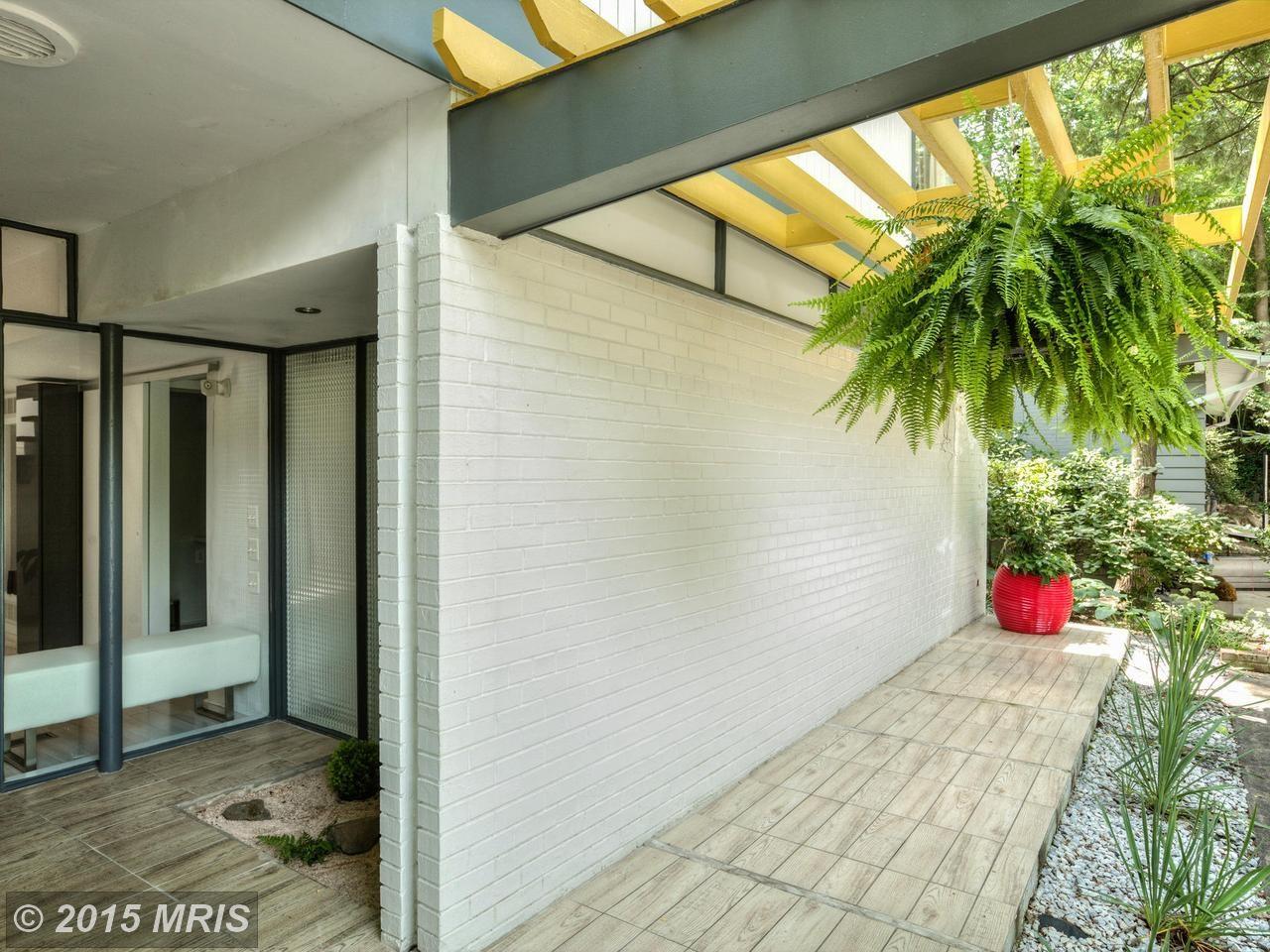 Брусчатая дорожка и каменный сад у входа подчеркивают красоту и умиротворенность модернистского дома.