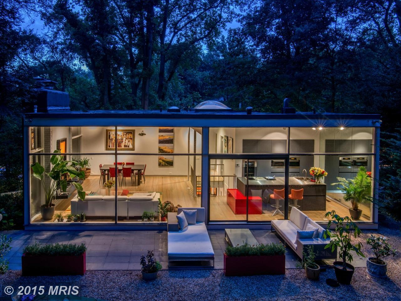 Дом в вечернее время, вид с дорожки в саду за домом. На плоской кровле видны световые фонари, улучшающие освещенность.