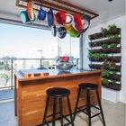 В этой части кухни с панорамным видом на город через огромное окно во всю стену приятно принимать гостей. Над кухонным островом висят кастрюли и сковородки. На стене растут разные съедобные травки. (кухня,дизайн кухни,интерьер кухни,кухонная мебель,мебель для кухни,фото кухни,мебель,интерьер,дизайн интерьера,современный)