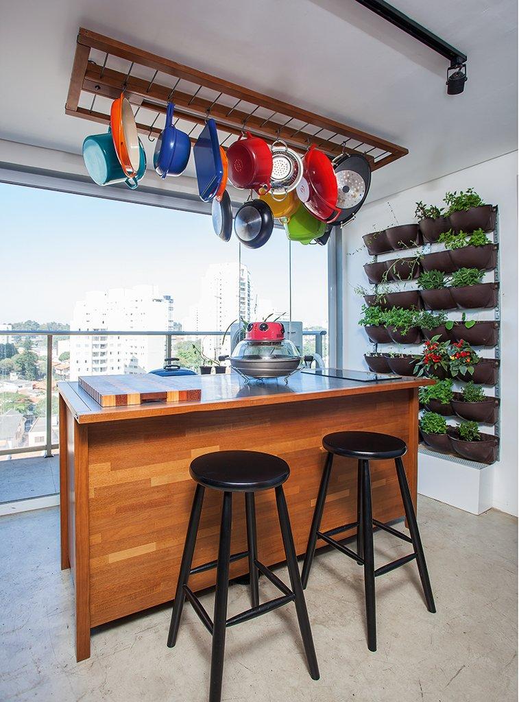 В этой части кухни с панорамным видом на город через огромное окно во всю стену приятно принимать гостей. Над кухонным островом висят кастрюли и сковородки. На стене растут разные съедобные травки.
