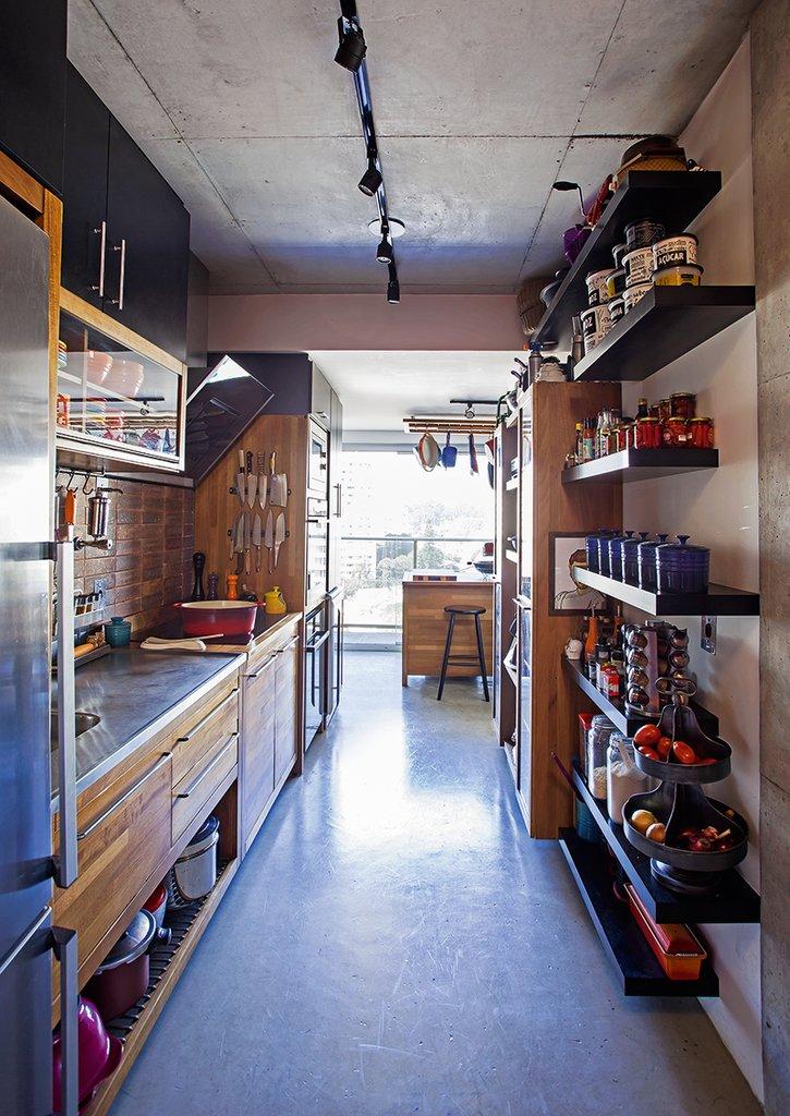 В кухне использованы практичные полированные бетонные полы. Вдоль стен огромное количество открытых полок и шкафов.