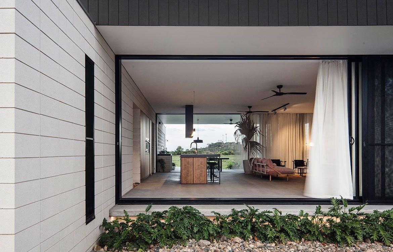 Большие сдвижные двери в противоположных стенах жилой комнаты, когда открыты превращают жилую комнату в крытую террасу проветриваемую теплыми бризами. Со стороны двора находится терраса с грилем.