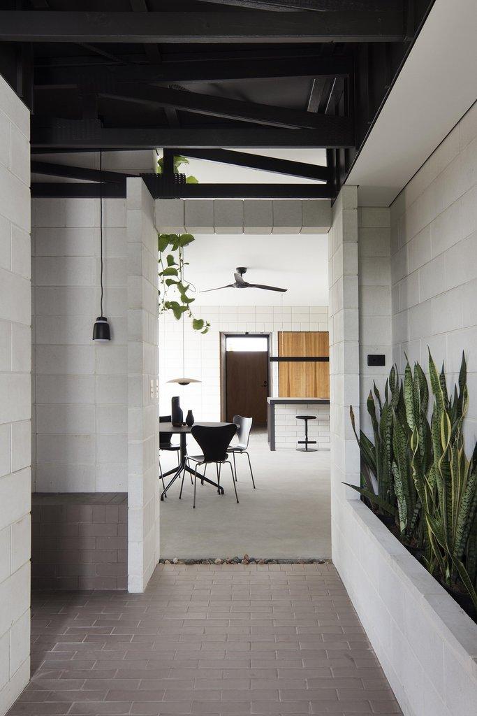 Главный вход в дом украшен зелеными растениями, а пол выделен брусчаткой.