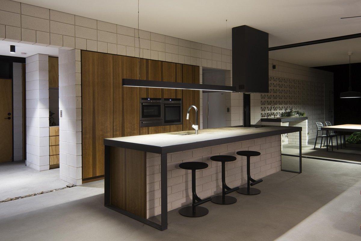 Кухня в вечернее время, рядом с кухней находится ярко освещенный обеденный стол на террасе.
