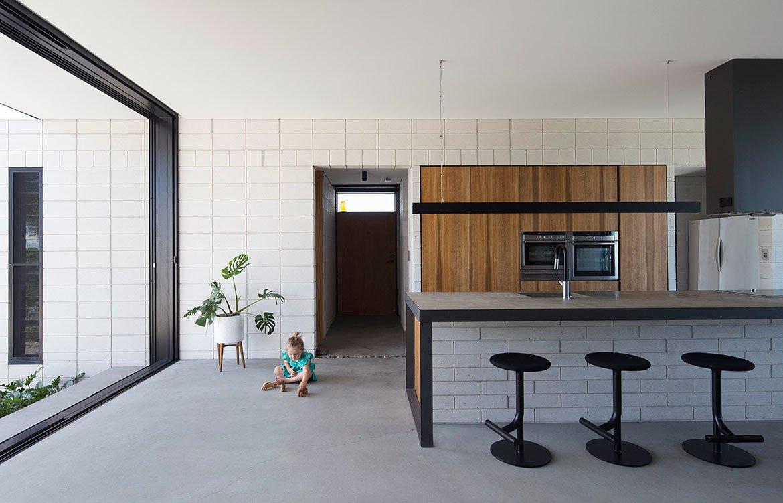 Кухонный остров является центральной частью кухни. Основа кухонного острова также выполнена из бетонных блоков. Это хорошо видно со стороны барной стойки.