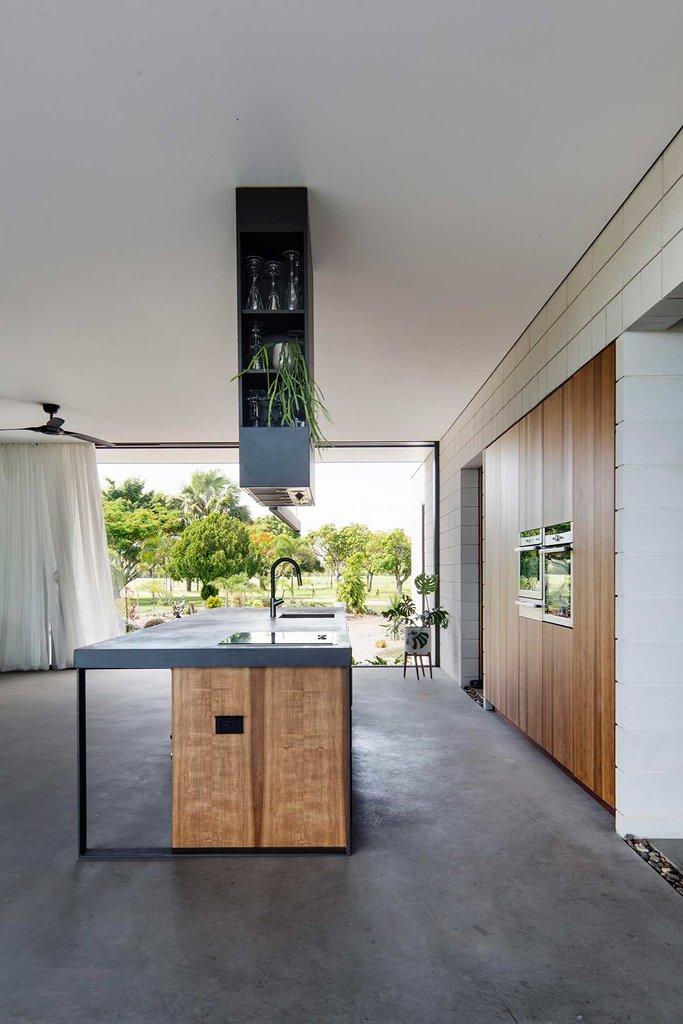 Минималистская кухня продолжает общее стилистическое оформление дома заданное не оштукатуренными стеновыми блоками.