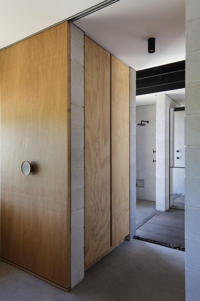 Сдвижная дверь с ручкой прямо в центе ведет в ванную комнату и хозяйскую спальню.