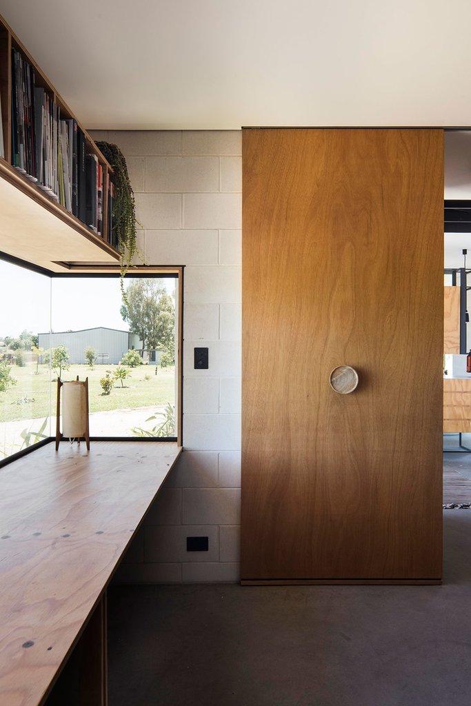 Современный домашний офис с рабочим столом в нише у окна. Над столом и угловым окном идеально вписалась вместительная книжная полка.
