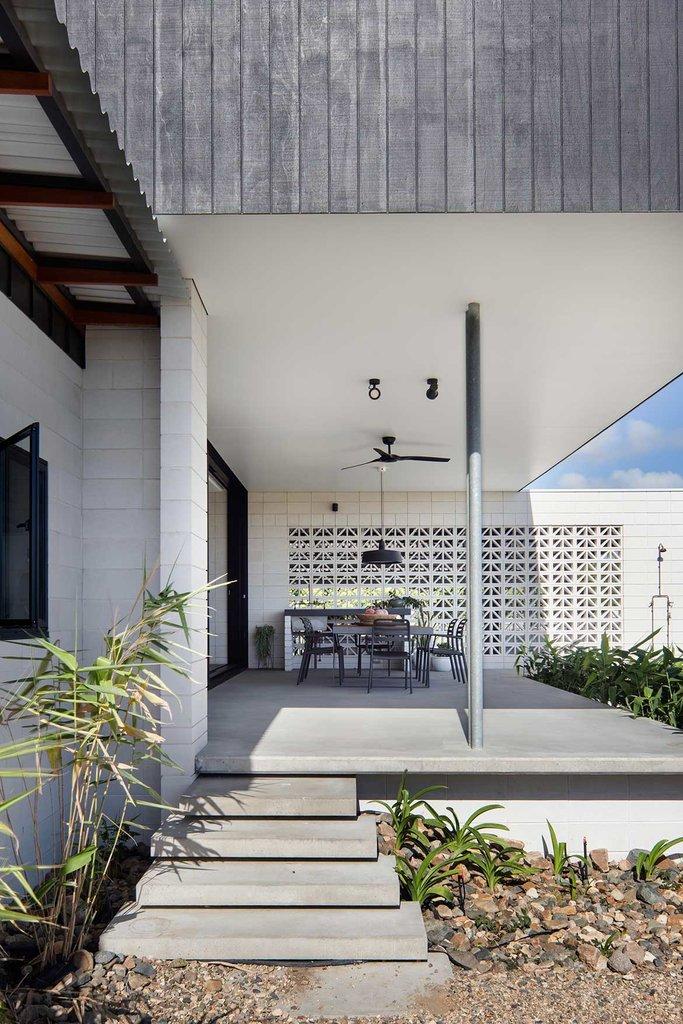 Высокая крытая терраса за домом с барбекю у экранирующей стены и потолочным вентилятором для жарких дней. Бетонный пол террасы сводит к минимуму усилия по уборке и обслуживанию.