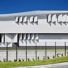Белая кафельная плитка украшает и нижнюю часть фасада дома, в то время как верхняя часть отделана белым сайдингом.