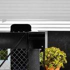 Черная калитка - вид с улицы. Рядом с калиткой расположился цветочный вазон.