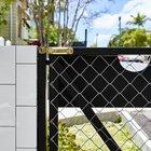 Элегантная и легкая калитка во двор дома с черным стальным каркасом и почти незаметной сеткой рабицей.