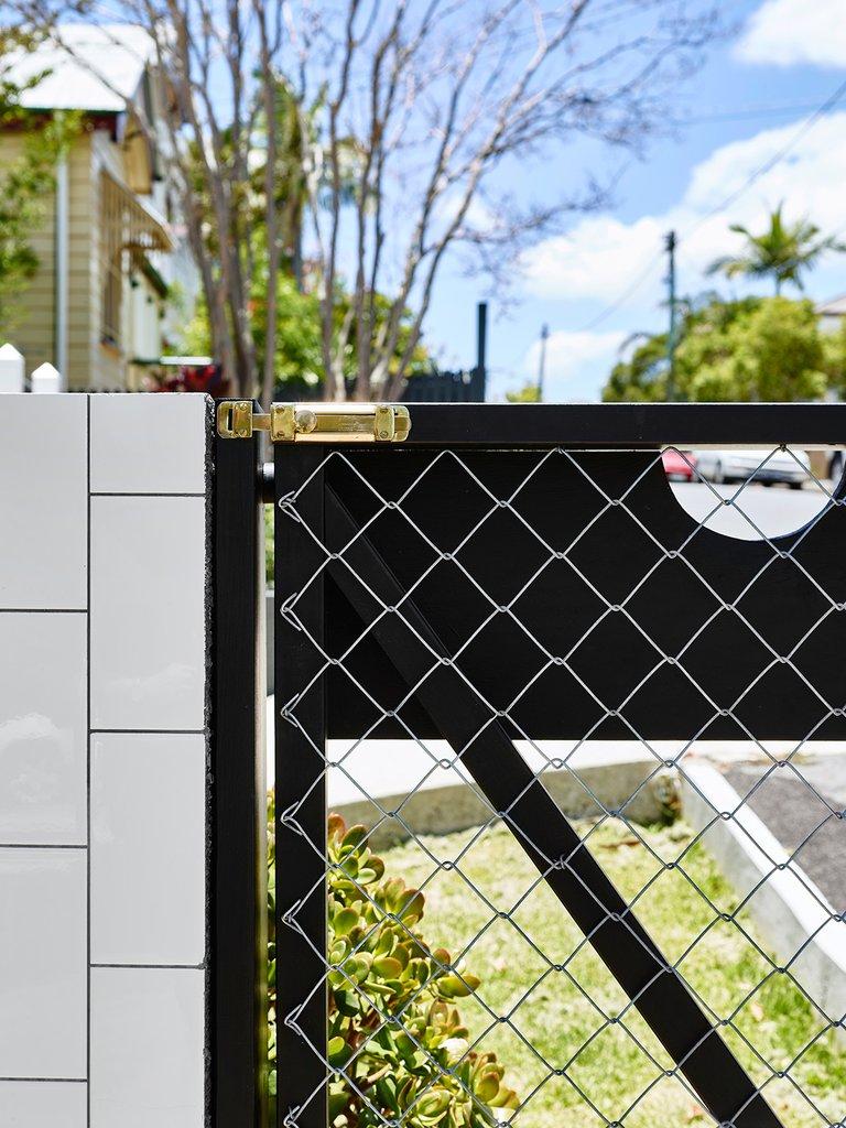 Элегантная и легкая калитка во двор дома с черным стальным каркасом и почти незаметной сеткой рабицей