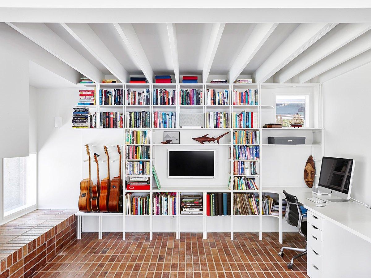 Гостиная или семейная комната выходит на задний двор к бассейну. В углу расположился домашний офис, у стены висящие книжные полки. Пол, как и широкий подоконник выполнены из клинкерного кирпича.