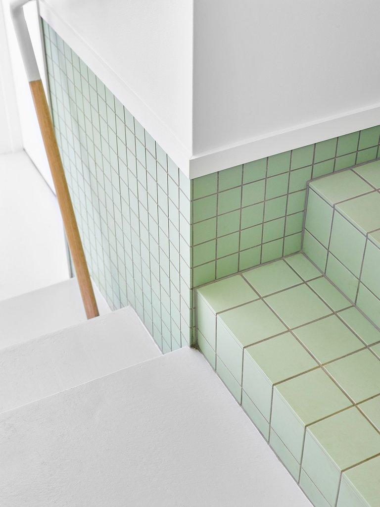 Кафель салатного цвета переходит в схожий кафель на ступеньках ведущих на второй уровень дома