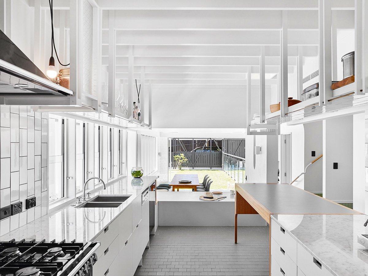 Кухня своим простым и чистым интерьером напоминает промышленную кухню. То что из столовой кажется барной стойкой из кухни видится скорее как скамья.
