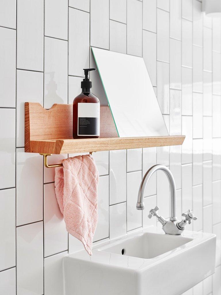 Маленькая полочка над крохотным умывальником в одной из ванных комнат дома