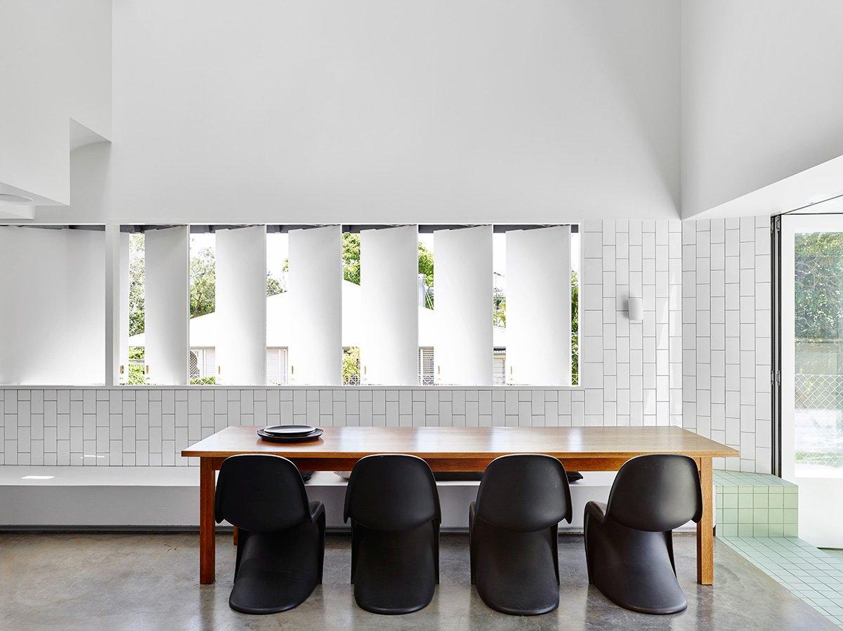 На стенах столовой использована та же практичная кафельная плитка, что и на кухне. Пол выполнен из полированного бетона, а полоска салатной кафельной плитки оживляет нейтральный интерьер