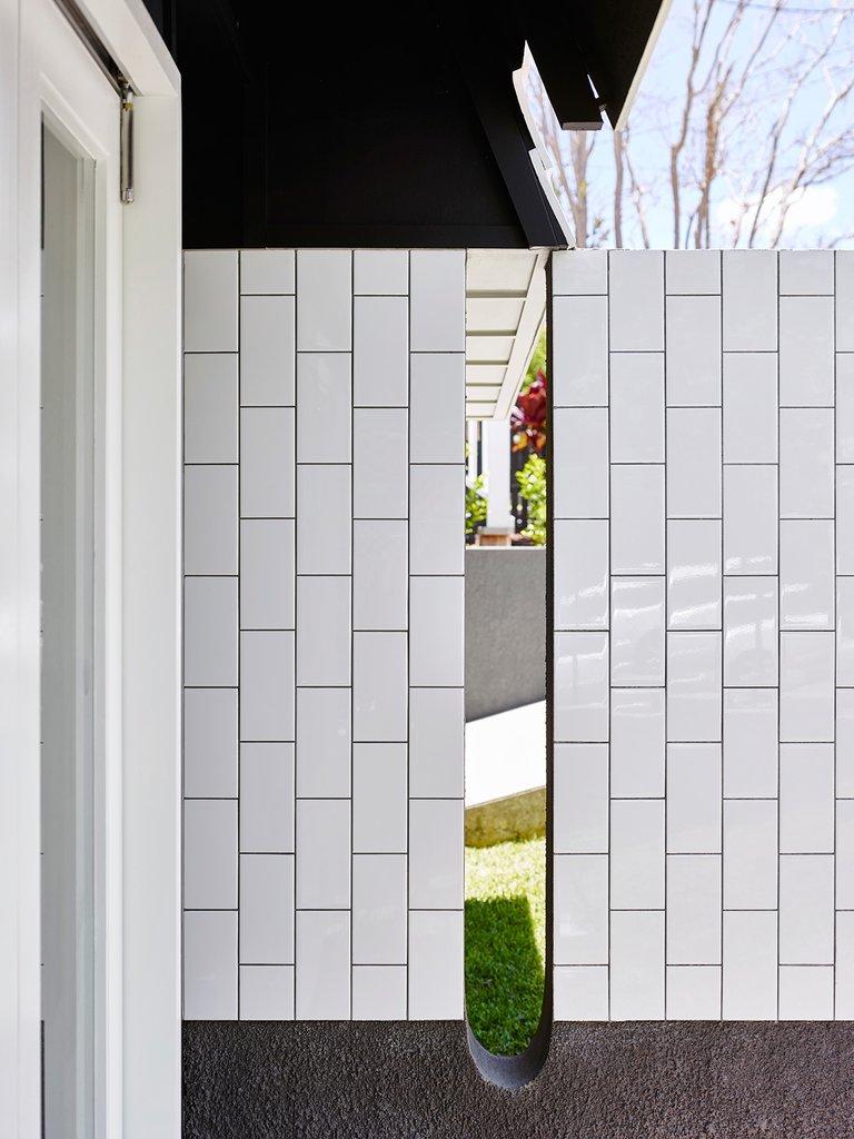 Обычный белый кафель применен в отделке фасада. Мало кто решается на такой дизайнерский прием.