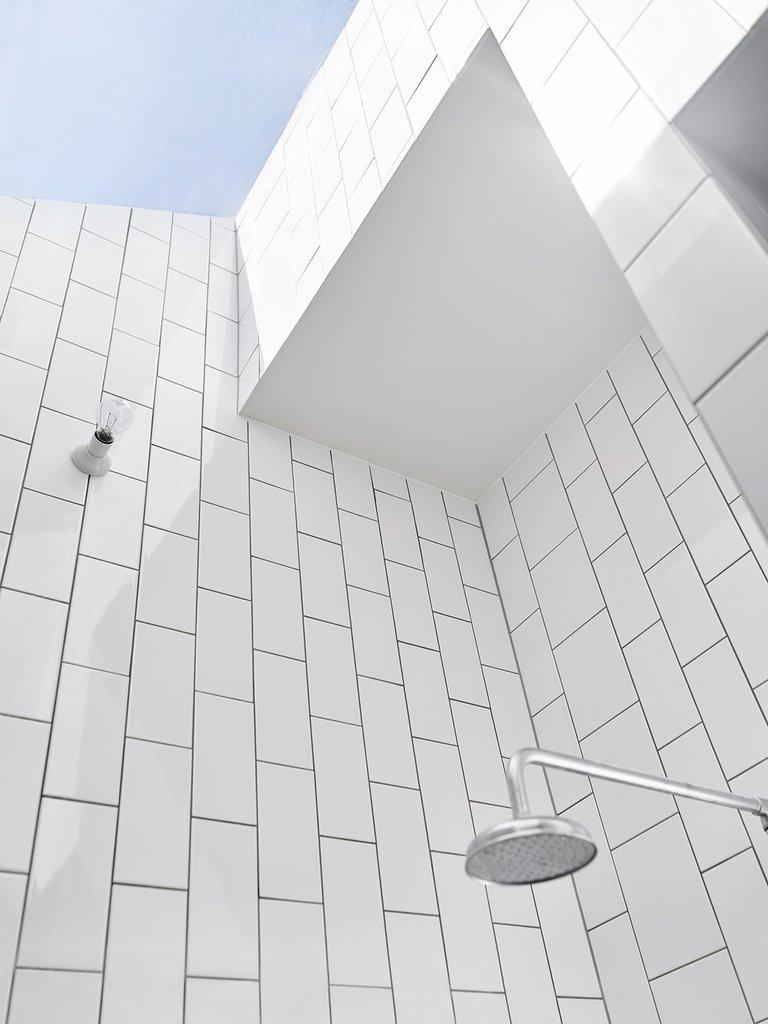 Остекленные потолки белой душевой заливают светом небольшое пространство.