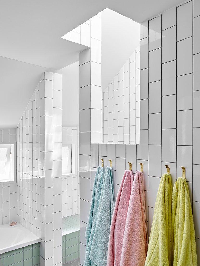 В качестве яркого декора в ванной выступают цветные полотенца, а белые стены выступают в роли нейтрального не надоедающего фона.