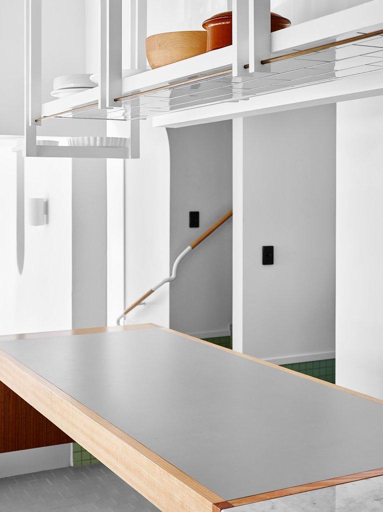 Висящие полки над поверхностью рабочего стола в кухне. Такие полки задавая форму пространству кухни одновременно не загромождают его.