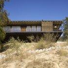 Дом возвышается над песчаным склоном, видимо подчеркивая отрыв от традиционного местного дизайна.