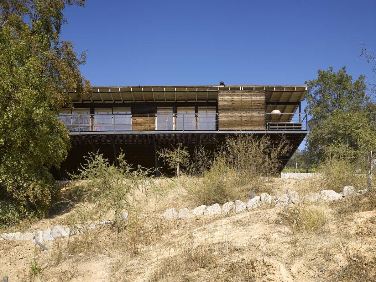 Дом возвышается над песчаным склоном, видимо подчеркивая отрыв от традиционного местного дизайна