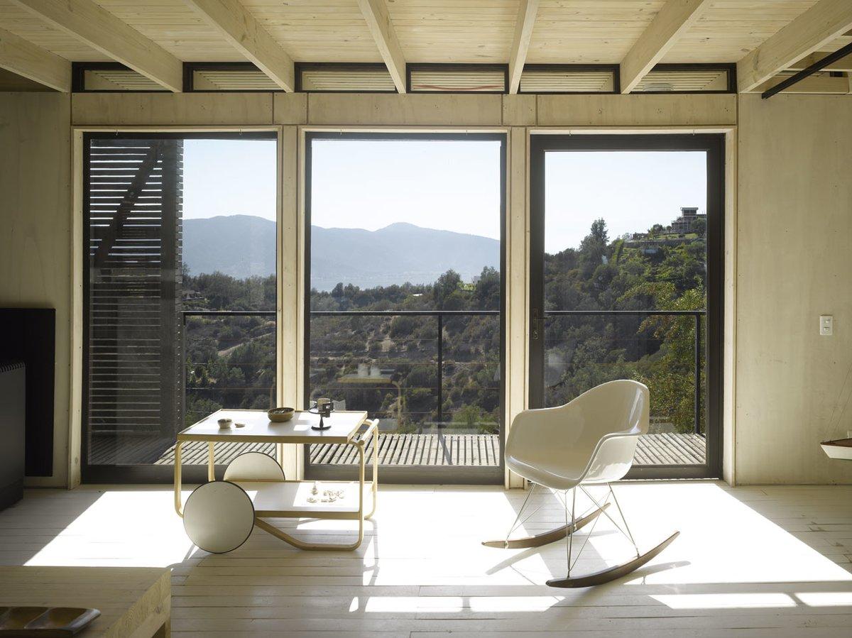 Мебель в доме, как и небольшие окошки под потолком между стропилами намекают на модернистские дома середины 20-го века служившие архитектору вдохновением.