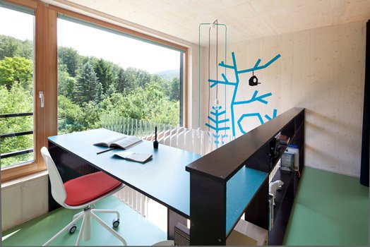 Проем в перекрытии второго этажа огражден книжными полками рабочим столом владельца. Домашний офис с большим окном в сад располагает к творчеству.